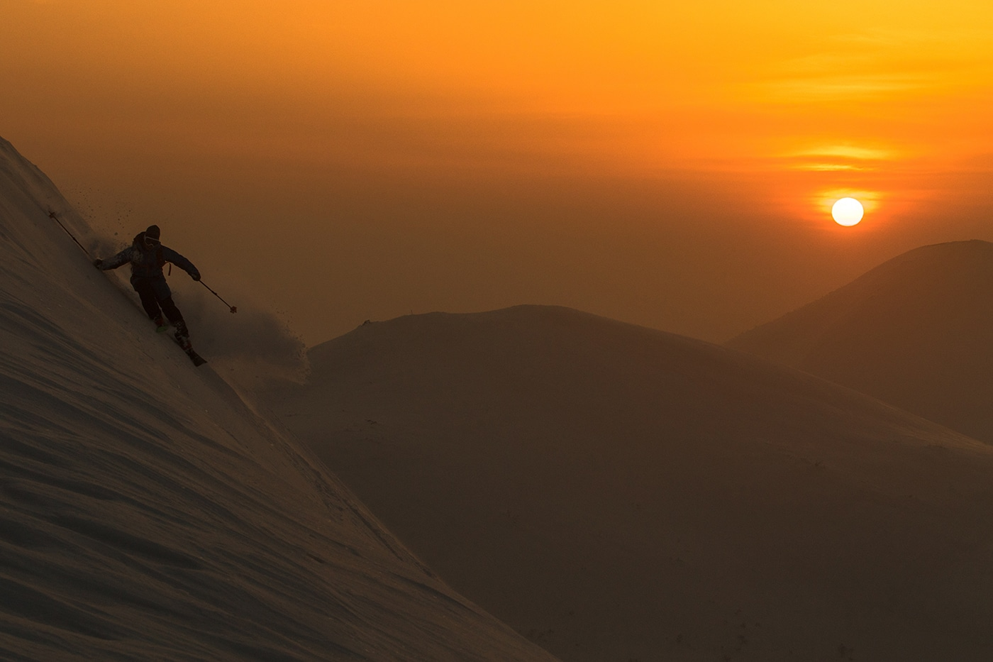 Incredible picture of Bine Zalohar skiing powder during sunset